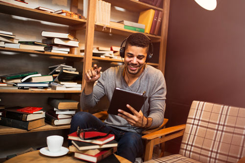 elearning man in library watching webinar on tablet