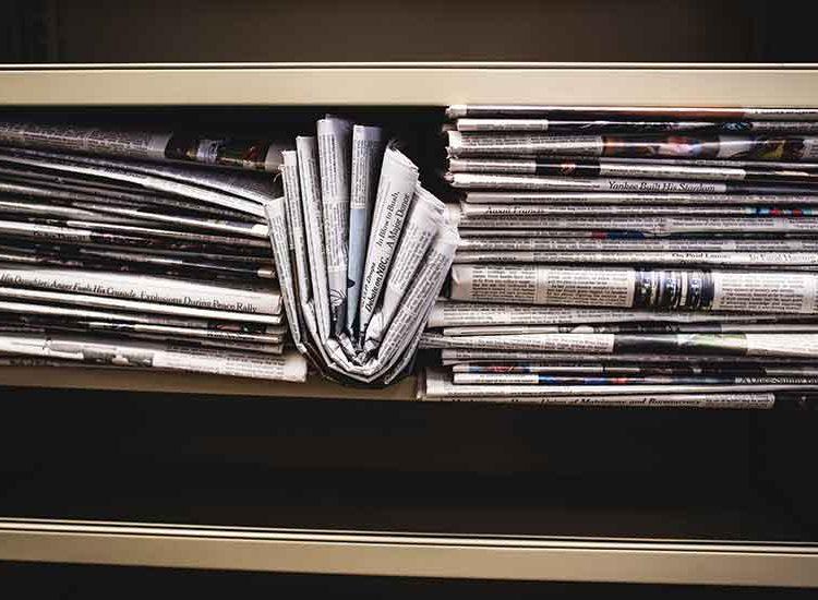 stack of newspapers on bookshelf